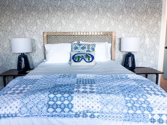 The large master bedroom has a queen bed with 3-inch memory foam mattress topper and cozy linens, USB charging stations at each nightstand, a large closet and dresser for your clothes, a desk, and laundry area.