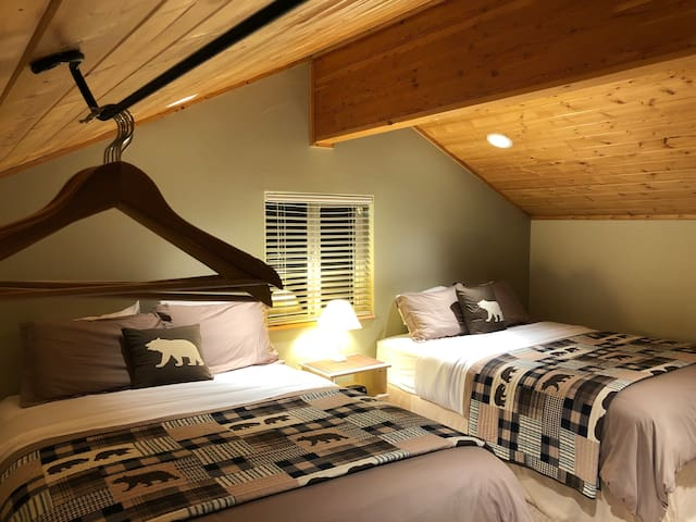 View of two queen beds in open loft.