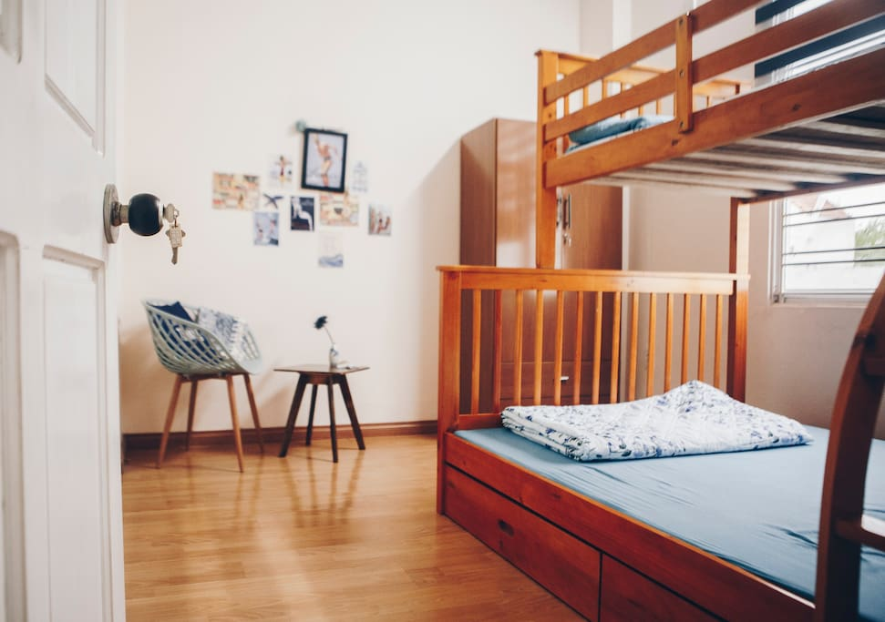 The room is equipped with a bed for three, a wardrobe, a chair and a coffee table