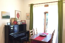Dining room, with the upright Kawai piano and dining table overlooking the wonderful green (with masses of pink in bougainvillea season!) side yard. And lots of art.