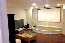 Movie theatre room with large drop down projector screen and surround sound.  Access to Netflix, Hulu, Apple TV and much more!