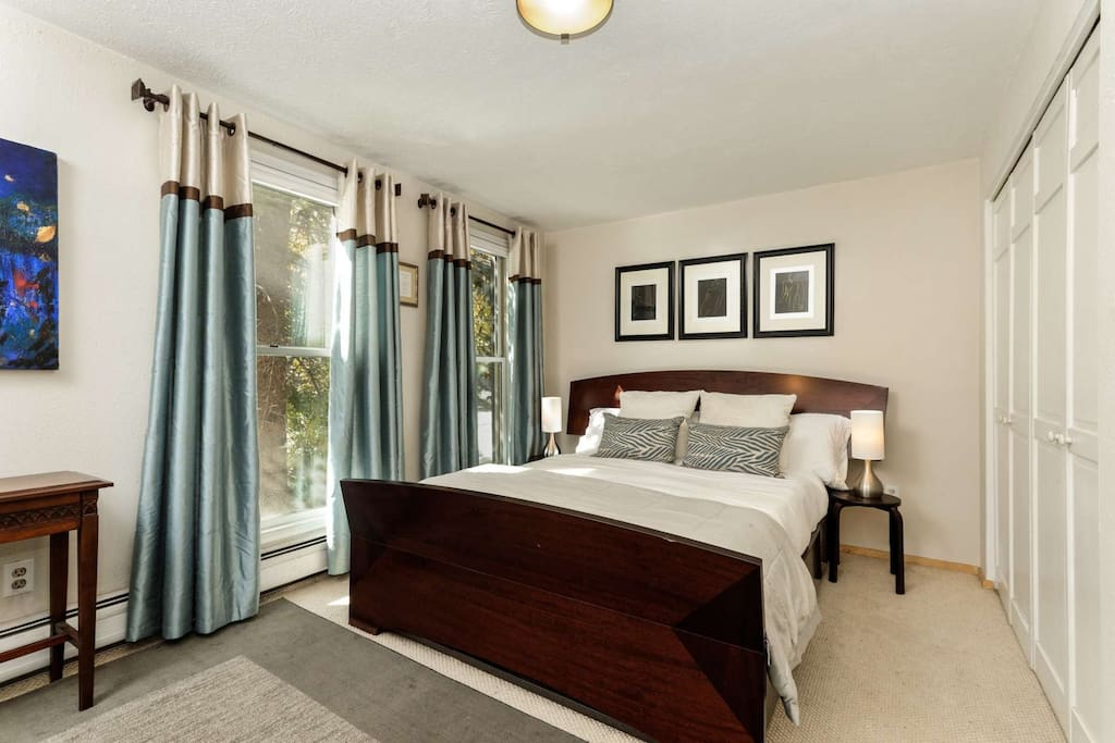 In the queen bedroom there are floor to ceiling windows to let in the warm sun and provide a beautiful view of the majestic trees outside