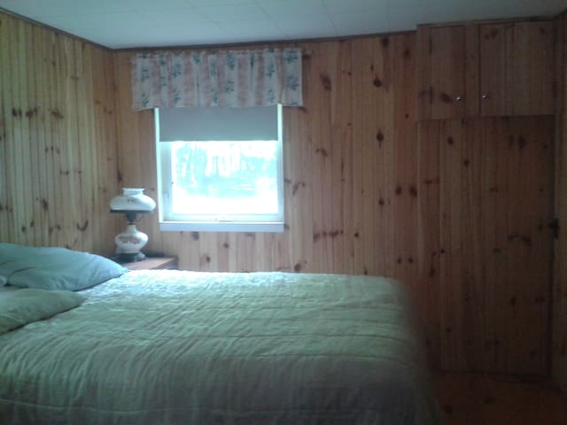 This is the master bedroom, the room is small and cozy, facing the long front  entrance/drive, that is nicely surrounded by a row of tall cedar trees.