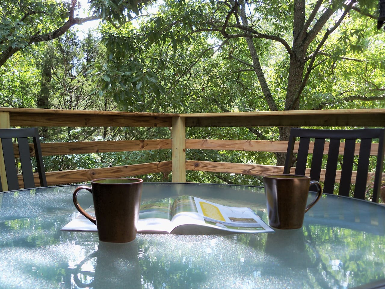 Relax on the front deck high among the trees.