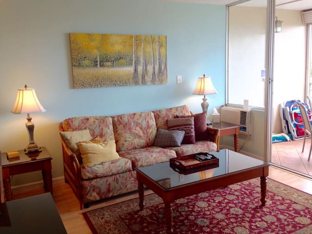A view of the living room sofa and coffee table from the main living space. The Lanai (deck) is to the right with floor-to-ceiling sliding glass doors.