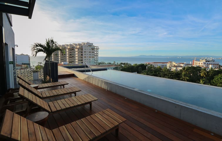 Just steps above the unit is a rooftop infinity pool and hot tub with sweeping views of Banderas Bay