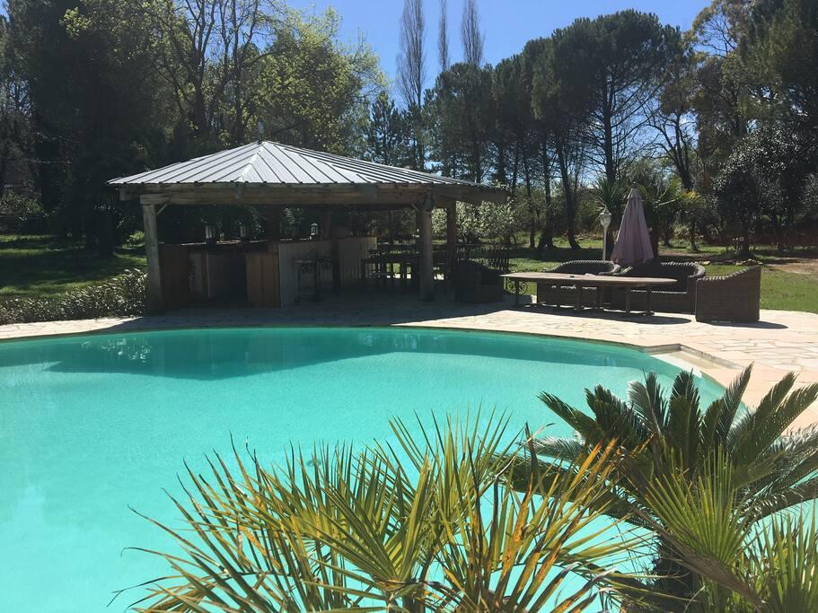 Piscine avec Pool house, salon extérieur, chaises longues.
