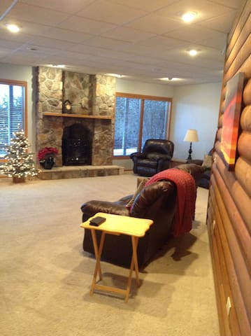 LIving room with lake view, fireplace and recliner sofa and love seat, 55 Inch smart television.
