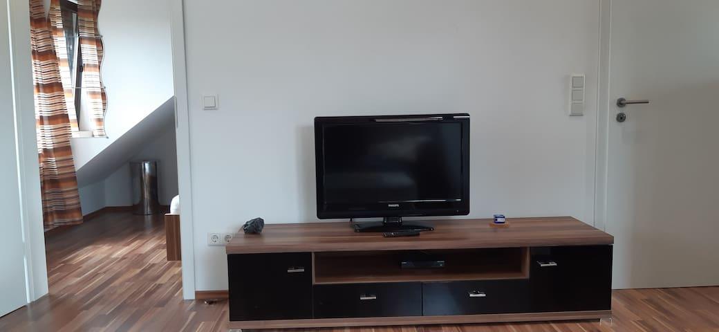 Wohnbereich mit TV, Tür zum  Schlafzimmer.