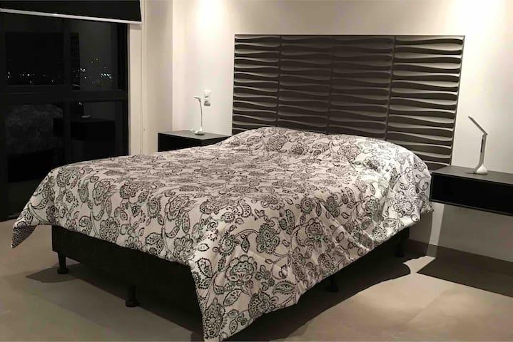 Dormitorio principal con una cama queen.  Ventana con vista a la ciudad. Cortinas blackout, aire acondicionado, baño privado, walking closet.