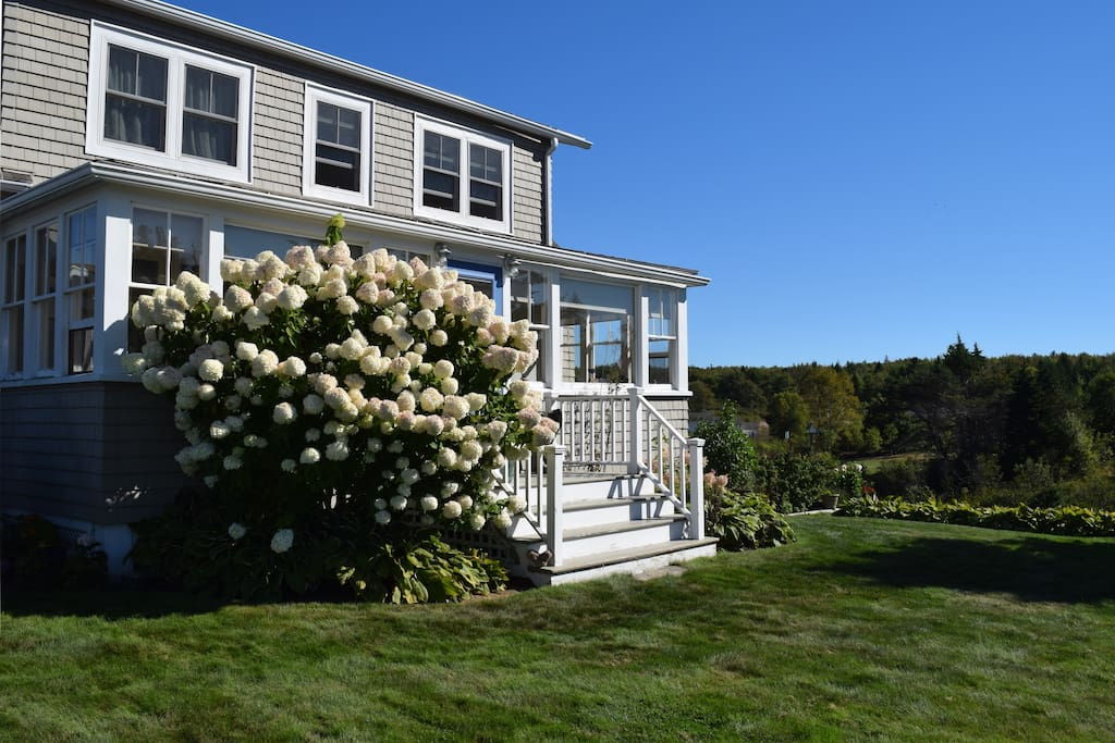 Gardens and flowering bushes surround the property.