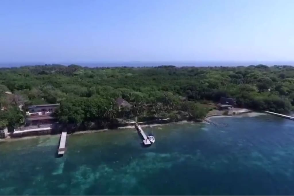 View from the sky. You can see the virgin transparent sea and the private dock. This photo shows the dimension of Isla Grande, and the green natural environment it offers.