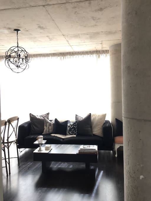 Cozy living room, open concept with high ceilings and access to outdoor patio.