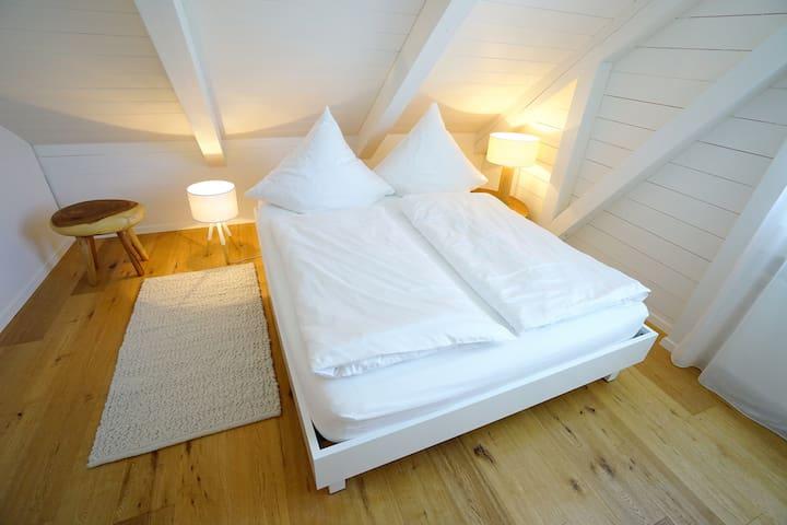 Feines Schlafzimmer mit hochwertigem Bett und Damast- bettwäsche