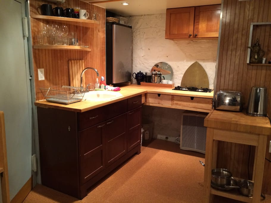 Kitchen with 2-burner stove top, sink, fridge.