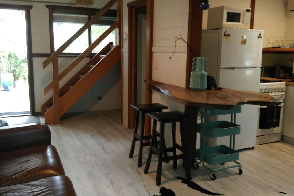 View of combined kitchen/lounge with stairs to loft bedroom
