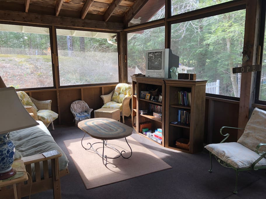 Screened in porch has a futon for sleeping and ample room for puzzles, games, reading, or watching our large movie collection
