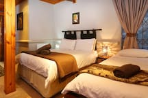 Spacious bedroom with double bed and single bed.