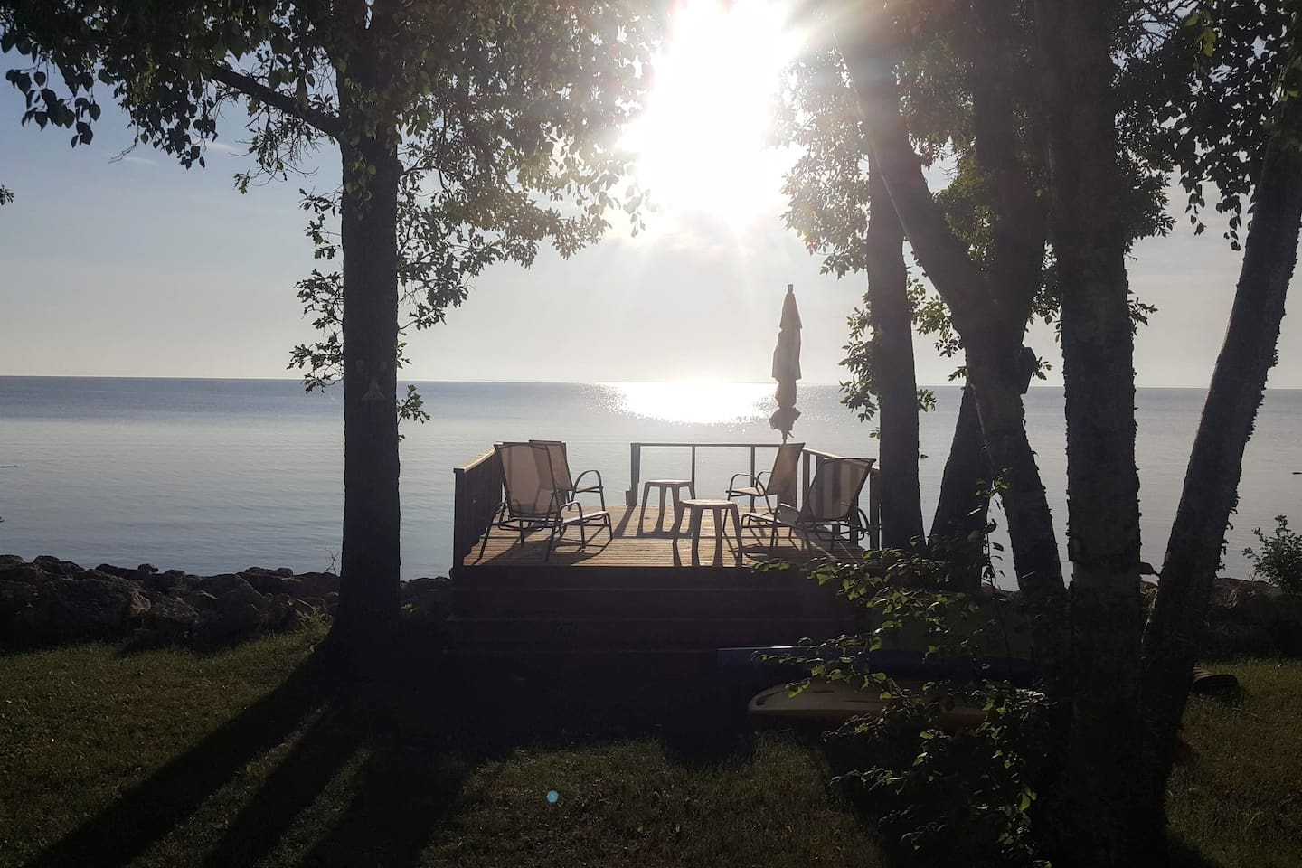 Morning view of private deck at the front of the cottage overlooking the lake.