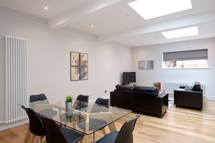 Comfortable Living Room with Leather Sofas and Dining Table