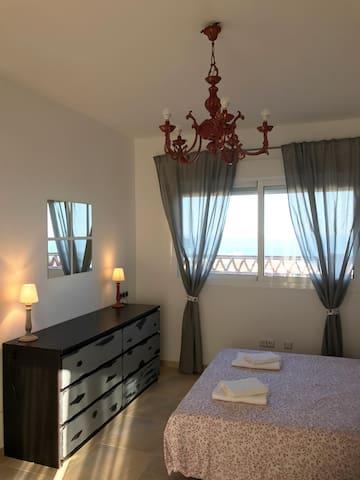 Dormitorio con cama de matrimonio, sofá cama, balcón, ventana a la terraza y vistas al mar.