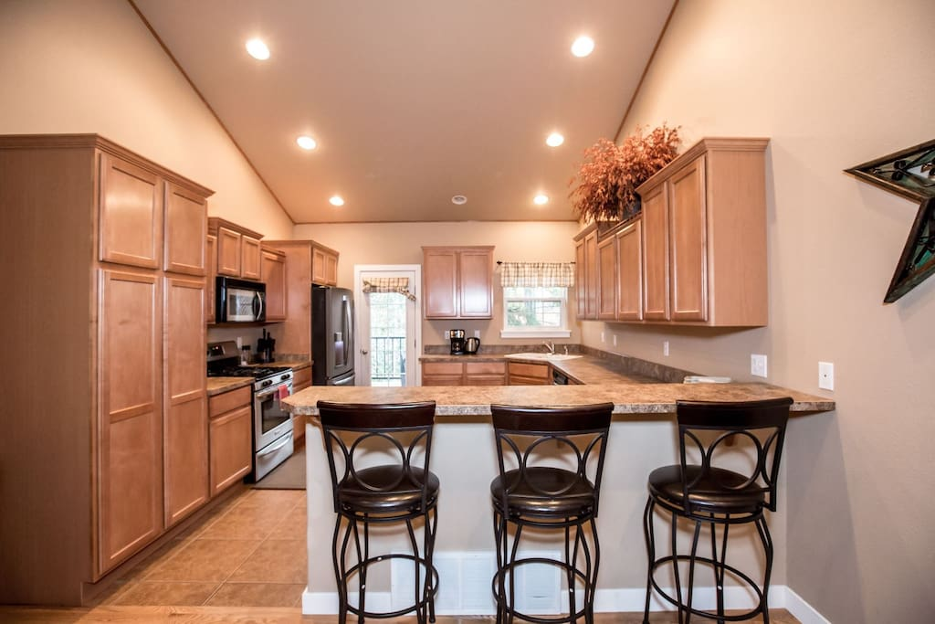 Spacious open plan kitchen with gas range and breakfast bar