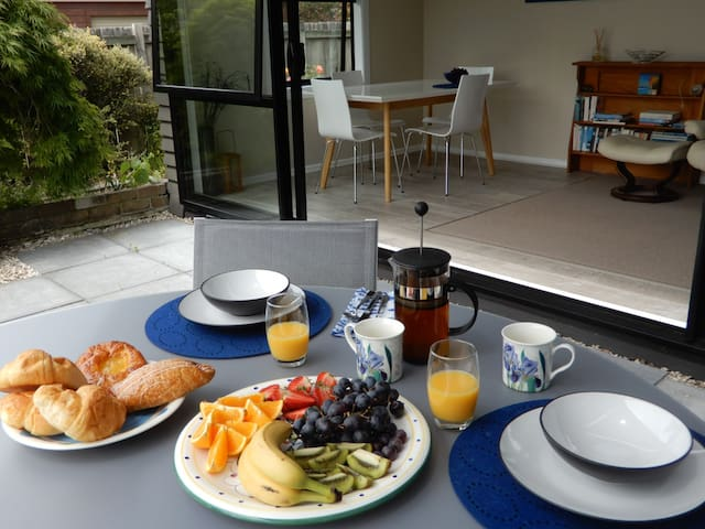 Indoor outdoor living with breakfast on the deck with views to Lake Rotorua.
