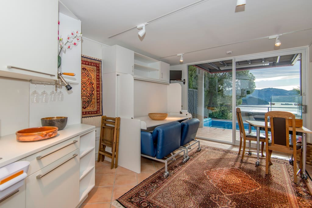 Studio: view towards terrace & pool. Double bed folded with desk in working position