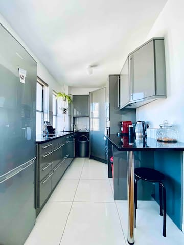 Fully equipped kitchen with a Stove, oven, microwave, dishwasher, Nespresso machine, kettle, blender, glassware, crockery and cutlery.
