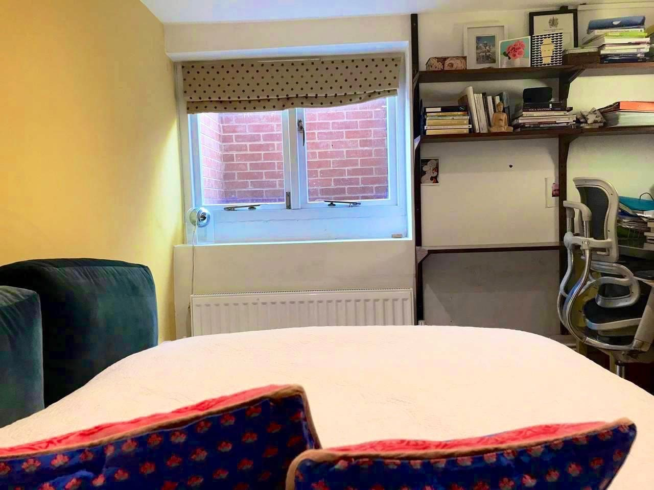 From the bed, 'view' is of egress window, and the desk. The room doubles as a study, so there are yoga and midwifery books and items stored on one side of the room and under the stairs, and a computer (not switched on) in the space.