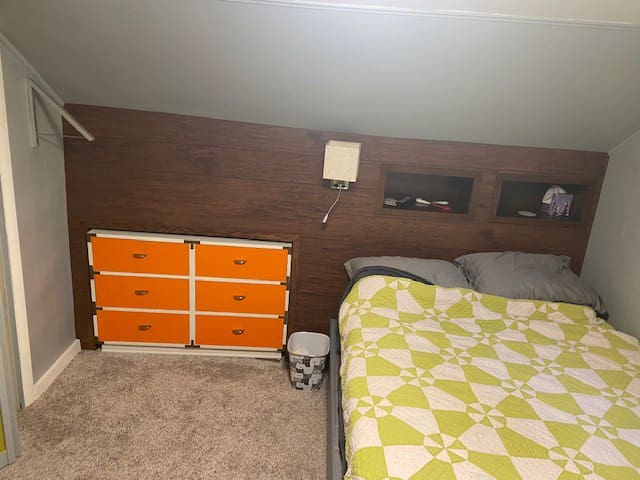 This room can be locked. To the left there is an extendable hanger space if needed. (Silver - folds down). Inside the left head board box is an outlet and USB plug. Open drawer space for your needs - orange dresser. Extra sheets in dresser to.