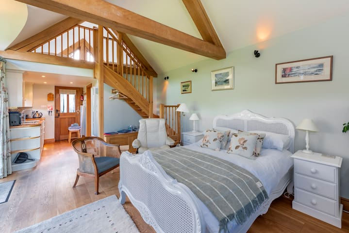 Double bed with view of mezzanine and kitchenette