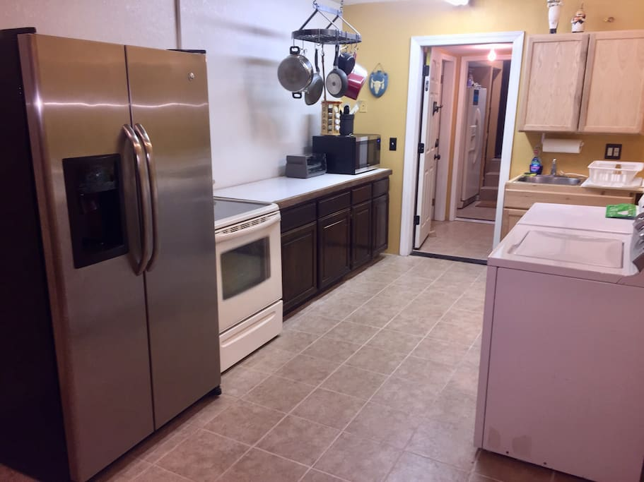 Large 10' x 22' kitchen/ dining area.  Complete with large stainless steel side by side refrigerator/freezer, oven/range, microwave oven, toaster oven, kitchen sink, & full size washer/dryer. The unit is furnished with pots, pans, cooking utensils as well as all plates, eating utensils, beverage cups and glassware.