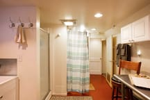 The bathroom area is separated by a curtain.   The kitchenette, bathroom and laundry are all one room.... separated from the bedroom by a door and hallway.