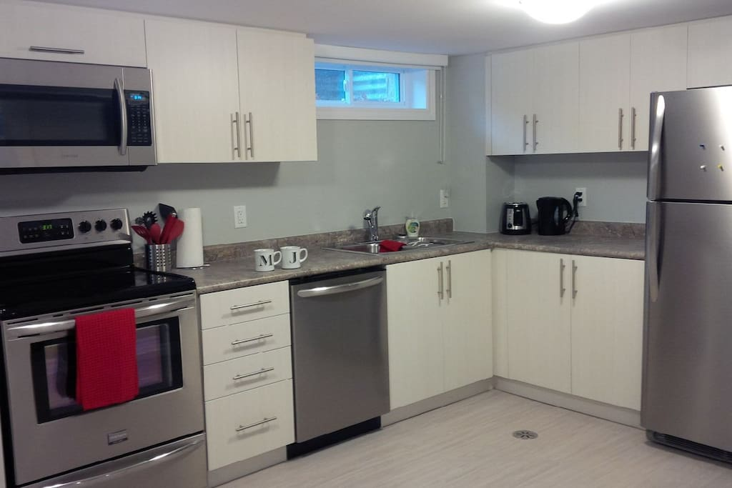 Fully equipped kitchen with stove, microwave, dishwasher and fridge.