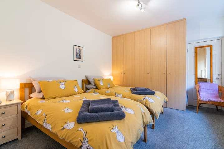 Beautiful bedroom with ample storage, twin beds and dressing table