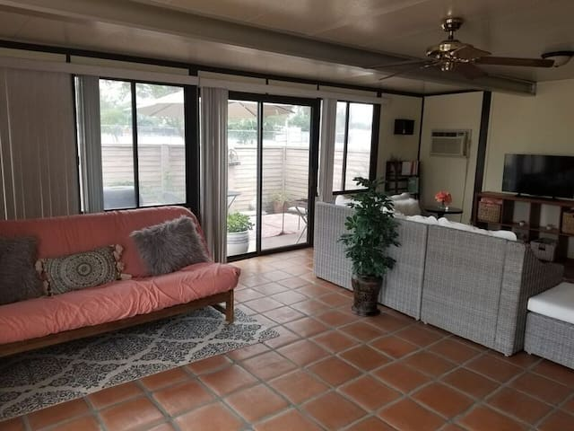 Sliding doors to outdoor patio, full futon couch and living room area (fan and air conditioning). The coral covered couch is a queen size futon. A queen air mattress is also available for additional guest.