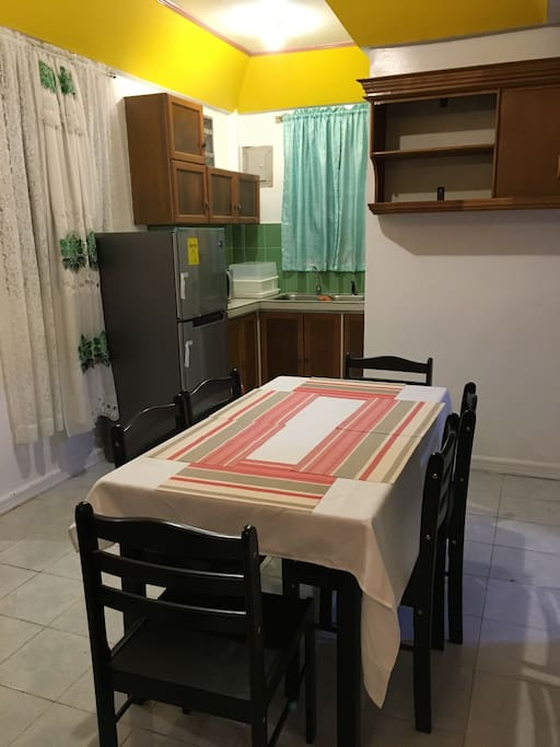 Dining and Kitchen area with Refrigerator, microwave, electric stove, covered dish container, hot and cold water dispenser