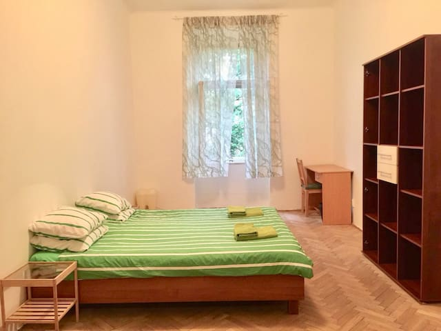 The room has the double bed, desk, bookshelf and wardrobe.