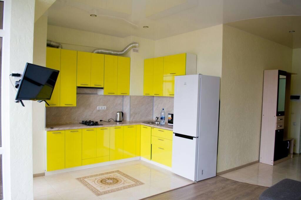 Кухня с газовой плитой, холодильником, чайником, микроволновой духовкой