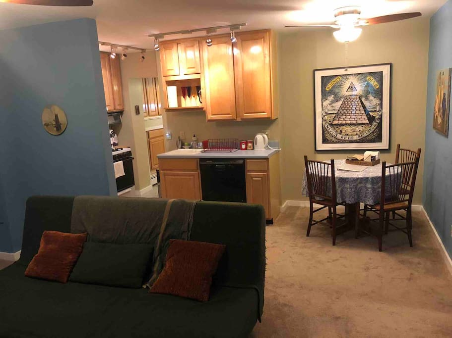 Main living area with dining table, kitchen, and hall to bathroom.