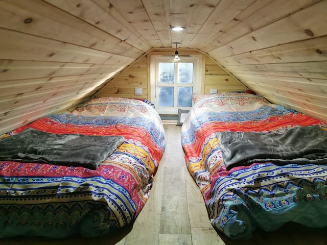 Single / Double loft bedroom with individual plug sockets and cosy throws.