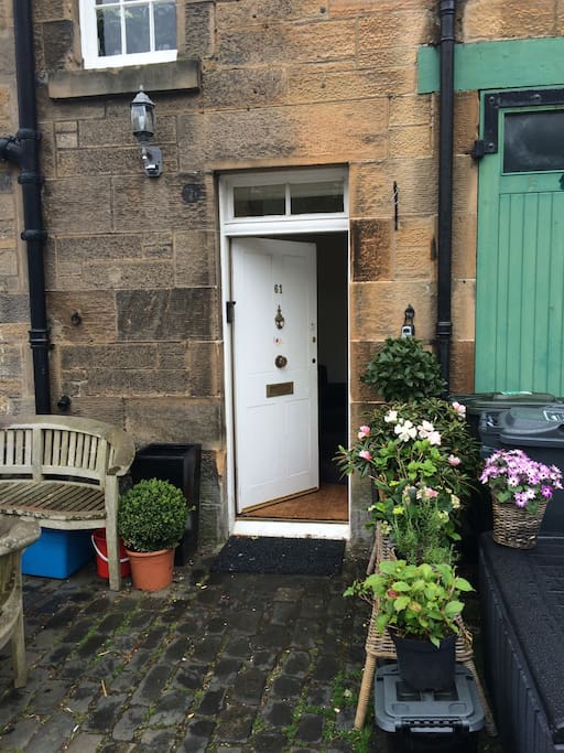 front door with seating area amongst the plants and cobbles