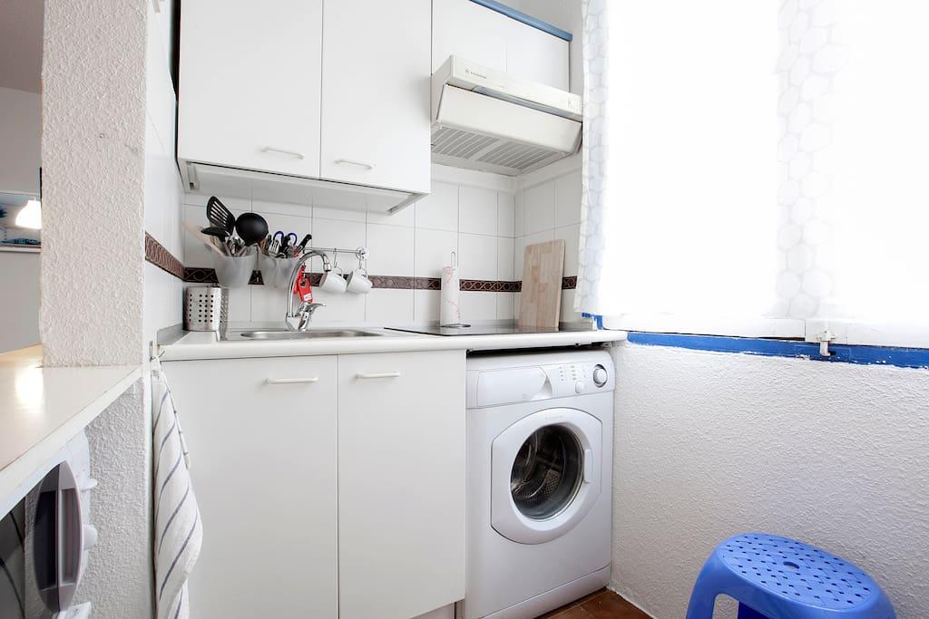 Cocina luminosa con lavadora, microondas y nevera.