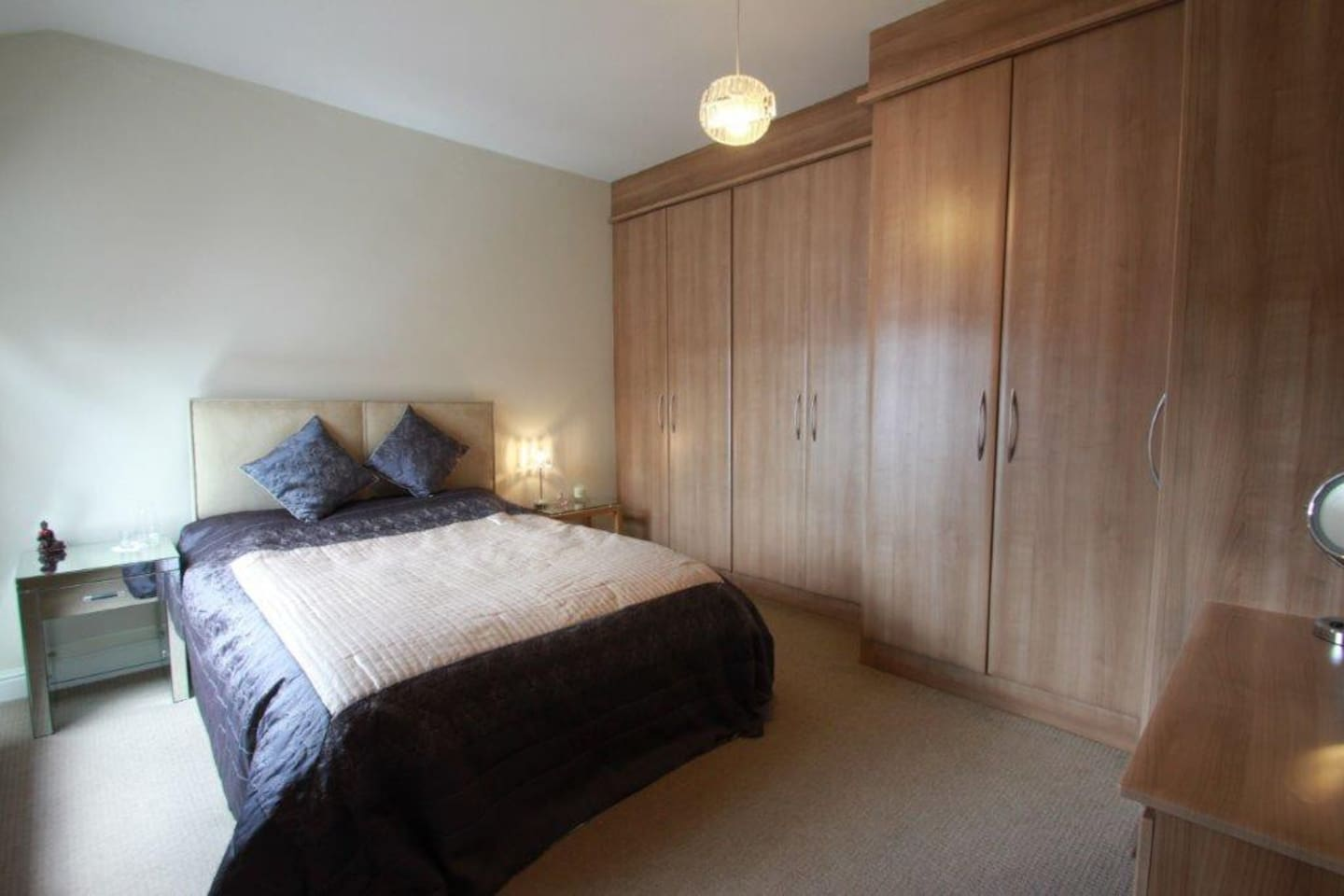 Large bedroom with wardrobe space and workspace. King-size bed