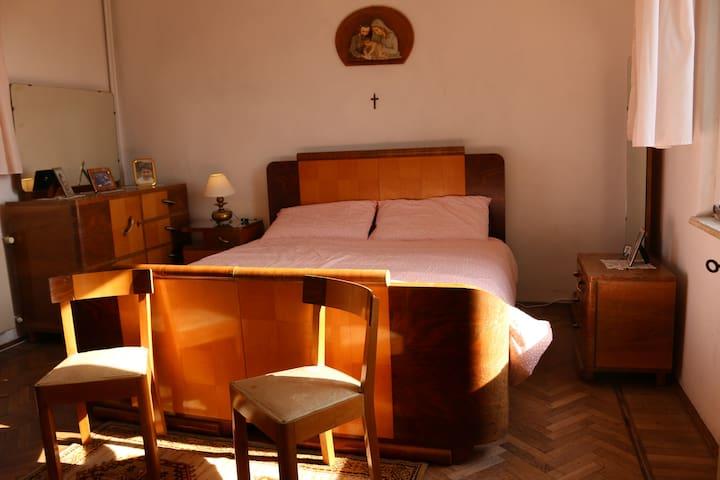 CAMERA AL PRIMO PIANO: Vista d'insieme dalla porta di ingresso. La stanza misura 4m. x 4m. E' dotata di due finestre, una che dà a sud e l'altra che dà a nord. Ai piedi del letto è possibile aggiungere un lettino da bambini/ragazzi fino a 14 anni