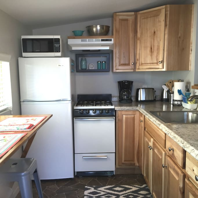 Kitchen with gas stove, frig and microwave
