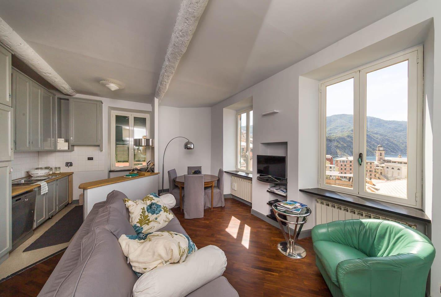 Il salone con angolo cucina, divano letto e smart tv