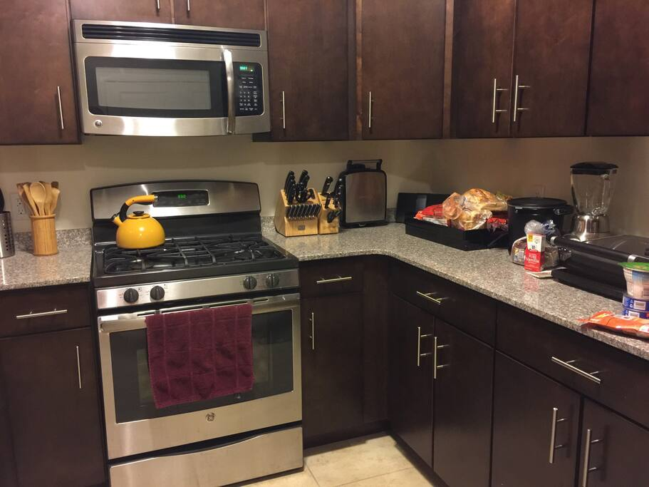 Full kitchen with a toaster, waffle iron, blender, mixer, cutting board, knives, deep fryer, tea kettle, pots and pans, utensils, microwave, refrigerator freezer and dishwasher.