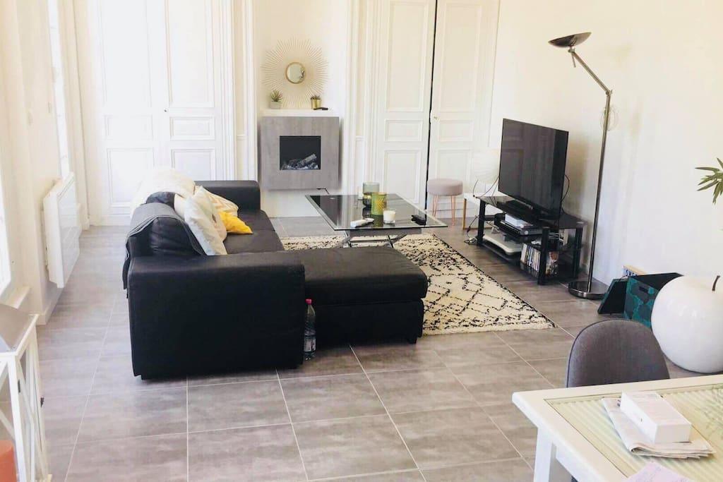 grande pièce à vivre très lumineuse de 35m2 comprenant salon, table à manger, cheminée électrique, télé, wifi et rangements